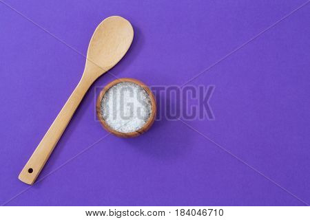 Salt in wooden bowl and scoop on purple background