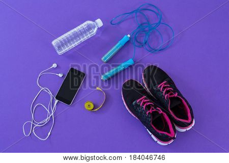 Fitness accessories, measuring tape and mobile phone with headphones on purple background