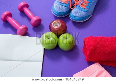 Fitness accessories with opened book and apples on purple background