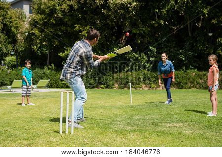 Happy family playing cricket in park on a sunny day