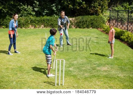 Family playing cricket in park on a sunny day