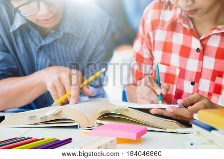 Young woman write the note. Young woman and man studying for a test or an exam. Tutor books with friends. Young students campus helps friend catching up and learning. People learning education and school concept.