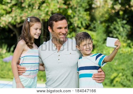 Father with son and daughter taking selfie from mobile phone in the park