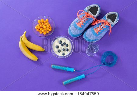 Shoes, banana, water glass, skipping rope and breakfast on purple background