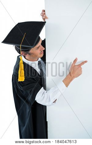 Male graduate student behind a panel and pointing with finger against white background