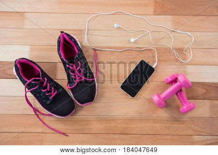 Mobile phone with headphones, shoes and dumbbells on wooden background