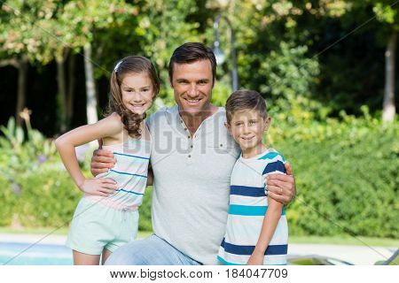 Portrait of smiling father with his son and daughter in the park