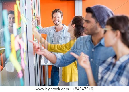 Smiling executives reading sticky notes on glass wall in office