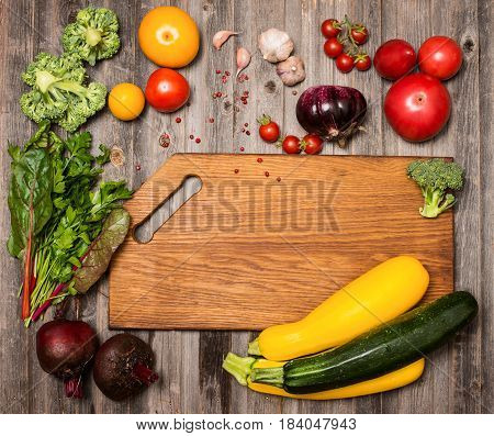 Empty cutting board and vegetables on weathered wooden background. Colorful ingredients for cooking on rustic wooden table around empty cutting board with copyspace. Top view. Retro styled.