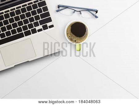 Office desk with cup of coffee and laptop computer on wooden table background. Top view with copy space for design