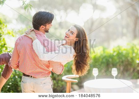 Man carrying woman in his arms in the restaurant