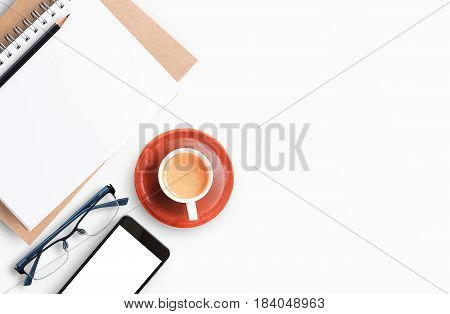 Modern white office desk table with laptop computer smartphone with black screen over a notebook and cup of coffee. Top view with copy space flat lay. Office desk table concept.