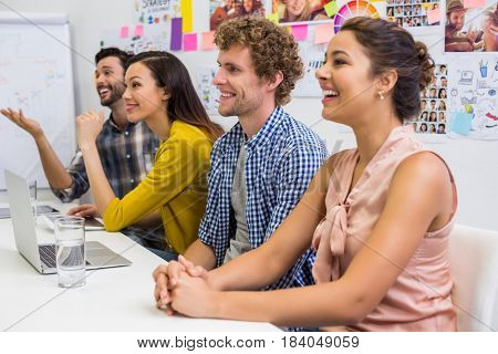 Smiling executives listening presentation in conference room at office