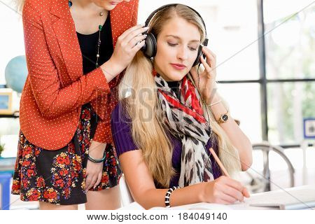 Two office workers at the desk listening to music