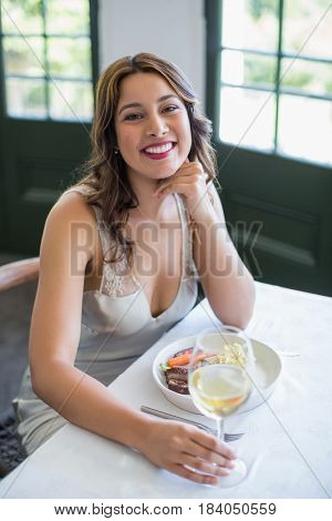 Portrait of woman smiling while holding wine glass in the restaurant