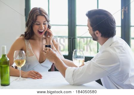 Man proposing a woman with a ring in the restaurant