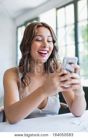 Beautiful woman smiling while using her mobile phone in the restaurant