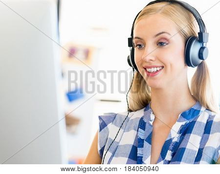Young woman working in office with headphones
