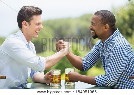 Friends greeting each other while holding beer glasses in the restaurant