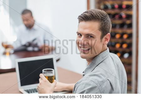 Portrait of handsome man holding beer glass while using laptop