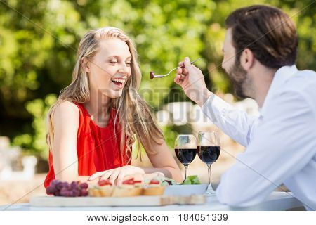 Man feeding a woman with fork in the restaurant