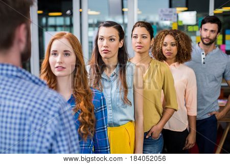 Serious colleagues standing in front of male executive at office
