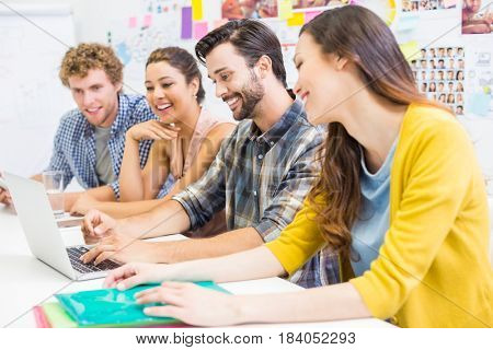 Smiling executives discussing over laptop in office