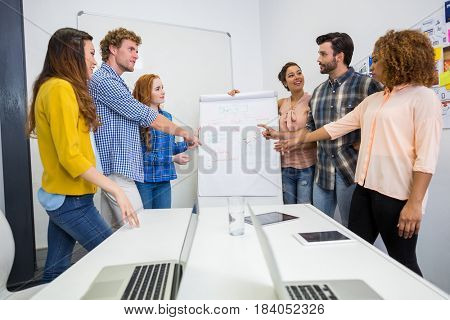 Executives discussing over flip chart board in conference room meeting at office