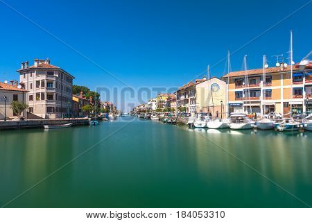 Grado - March 2016, Italy: Canal with sail boats lying on water in small Italian town of Grado