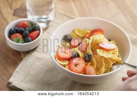 female teen girl hand eats healthy breakfast with corn flakes and berries, slightly toned photo