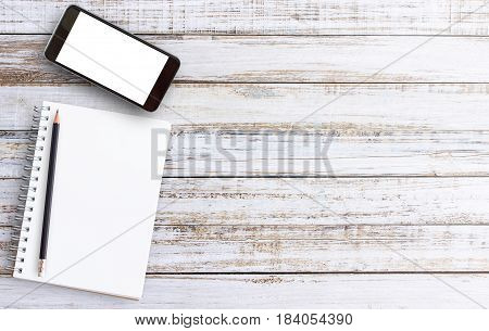 Flat lay close up clean open notebooksmart phone on top of wooden table with copy space below for text.