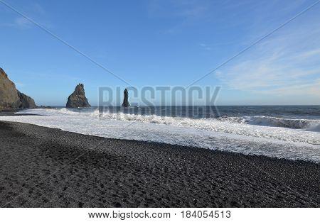 Towering black sea stacks located off the shore of Reynisfjara Beach in Iceland.