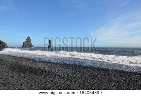 Waves lapping the black sand shore of Reynisfjara Beach in Vik Iceland.