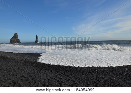 Gorgeous black sand beach known as Reynisfjara Beach with waves rolling ashore.