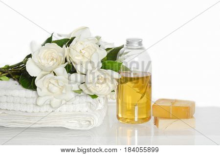 Spa setting with gardenia on towel,soap, massage oil
