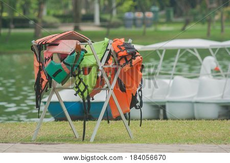 Many wet life jacket hanging on clothes line with lake background.