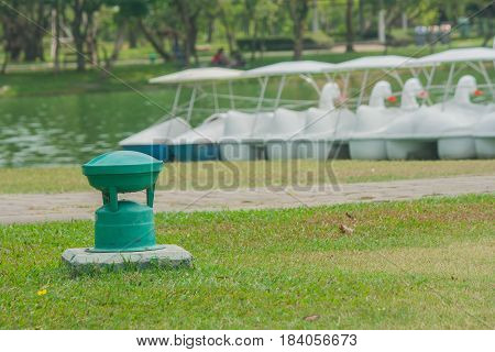 Green garden lamp for outdoor on green grass in public park.