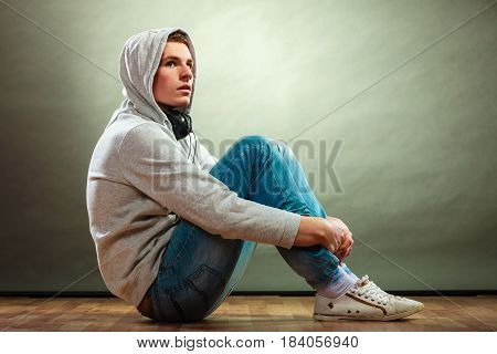 Music passion youth concept. Serious hooded man teen boy with headphones sitting daydreaming on floor grunge background
