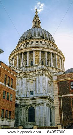 View of St Paul's cathedral from between neighbouring buildings in London.