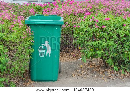 Large green wheelie bin at public park with bush and pink flowers background.