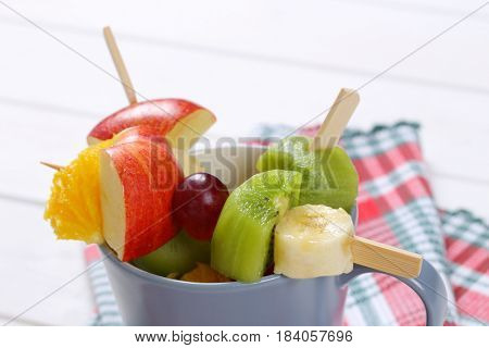 cup of fresh fruit skewers on checkered dishtowel - close up