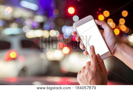 Female hands holding blank screen smartphone at street night in city. copy space for design