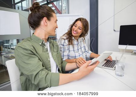 Smiling executive using laptop and digital tablet in conference room at office
