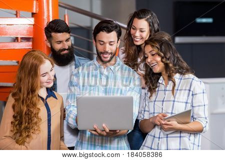 Happy executives having discussion over laptop in office