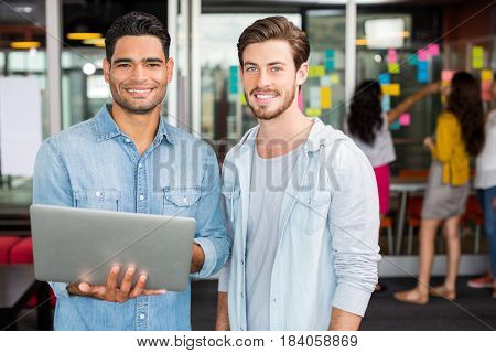 Portrait of happy male executives using laptop in office