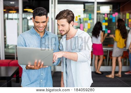 Male executives discussing over laptop in office