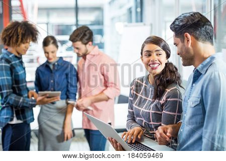 Male and female executives having discussion over laptop in office