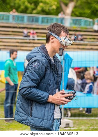 Kyiv Ukraine - April 29 2017: Drone racing pilot is controlling a flying drone with remote control in Kyiv Ukraine.