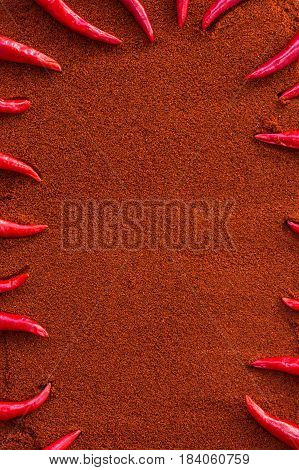 chili red hot pepper, concept of popular spice - sharp tips of red chili peppers laid out in a frame on background of dry mix of brown curry powder, flat lay, top view, free space for text