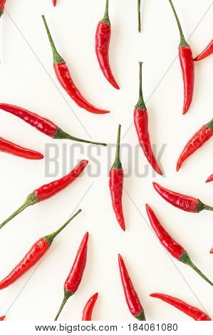 food pattern, popular spices concept - closeup beautiful red hot chili peppers filled white background, green tails, collage of freely lying peppers, top view, flat lay